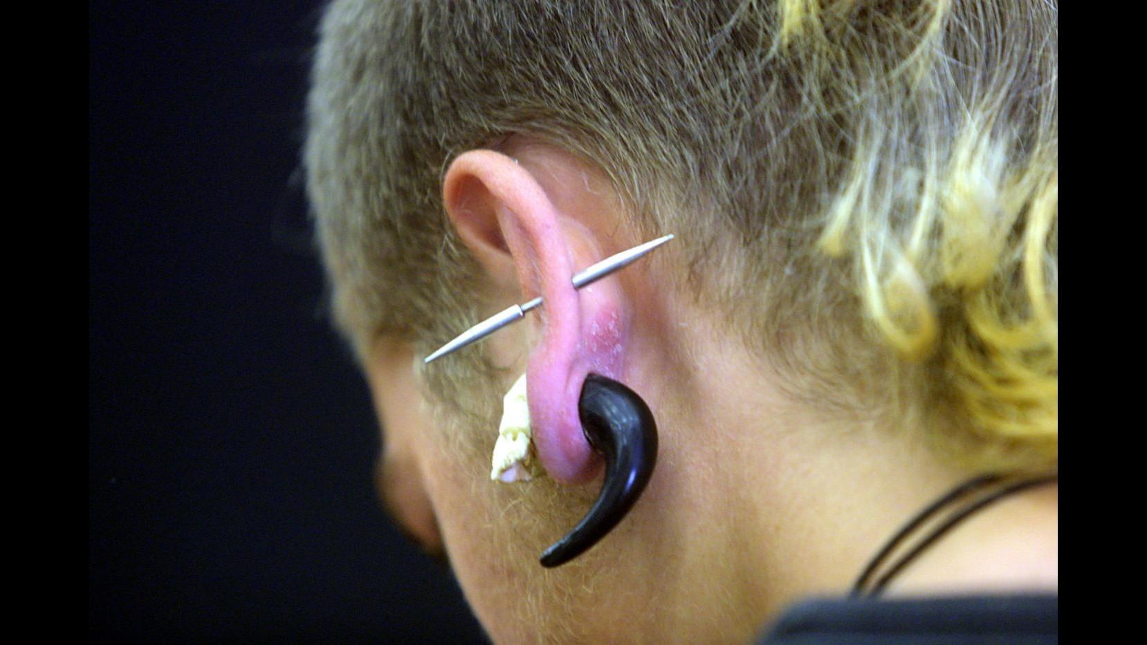 Catania, tatuaggi e piercing abusivi: denunciato 23enne