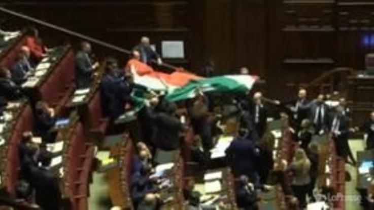 FdI srotola maxi bandiera tricolore in aula: bagarre alla Camera