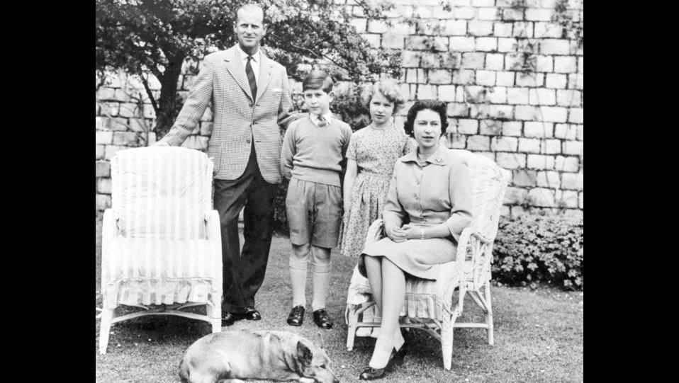 La regina Elisabetta posa per una foto di famiglia con i principe Filippo e i figli Carlo e Anna nel giardino del Castello di Windsor; con loro il cane Sugar ©