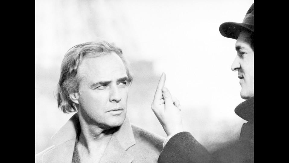 Il regista con Marlon Brando sul set del film 'Ultimo tango a Parigi' (1972) ©