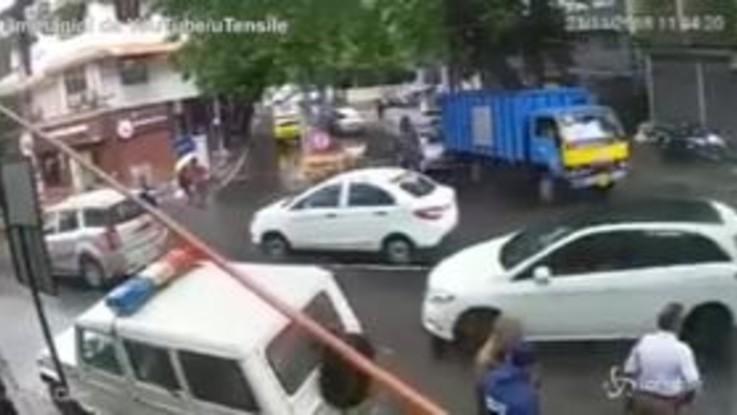 India, motociclista rischia scontro con il camion: vigile lo 'placca' e lo salva