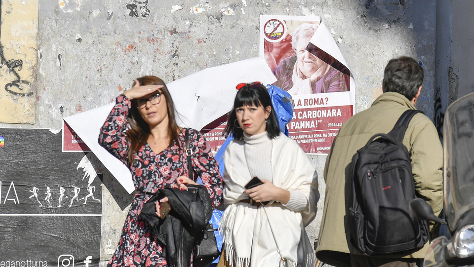 Due turiste e alle loro spalle il manifesto della Sora Lella ©