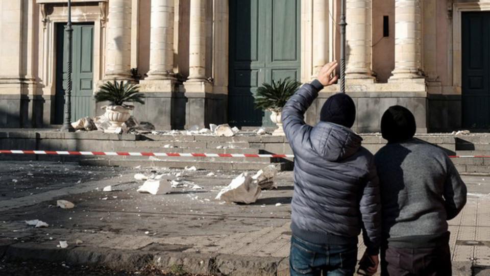 Due cittadini osservano i danni del terremoto ©