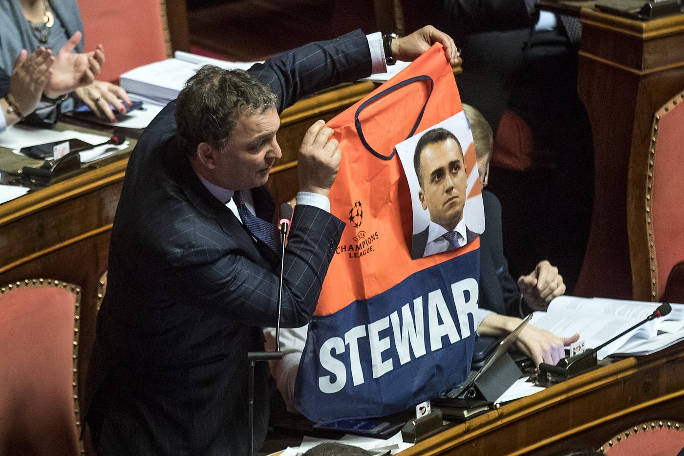 Decretone, bagarre in Senato. Saccone (FI) mostra gilet da steward con la foto di Di Maio