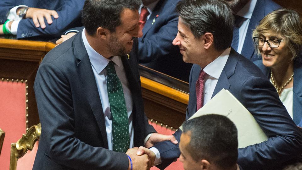 Matteo Salvini e Giuseppe Conte si stringono la mano prima del discorso del premier ©