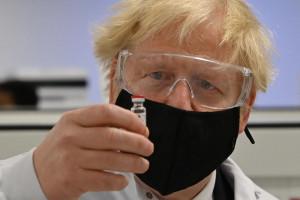 Il primo ministro Boris Johnson osserva i lavoratori che eseguono test di qualità del processo di produzione dei vaccini Covid-19