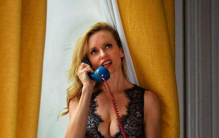 Justine Mattera in autoreggenti e body, al telefono.