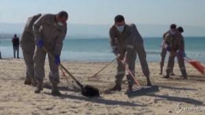 Volontari puliscono le spiagge dopo lo sversamento di petrolio