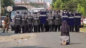Suora in ginocchio davanti alla polizia