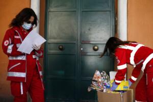 le volontarie consegnano i pacchi ad una mamma