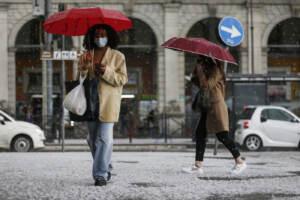 Passanti con gli ombrelli durante una grandinata