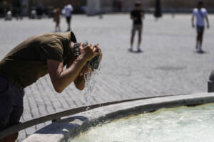 Caldo a Roma, i pochi turisti si rinfrescano nelle fontane