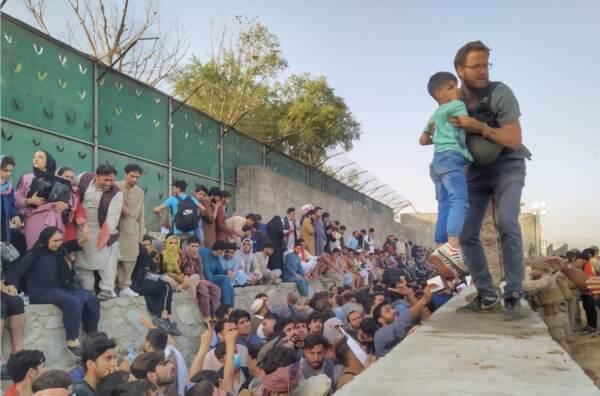 Il console Tommaso Claudi aiuta un bambino afghano all'aeroporto di Kabul